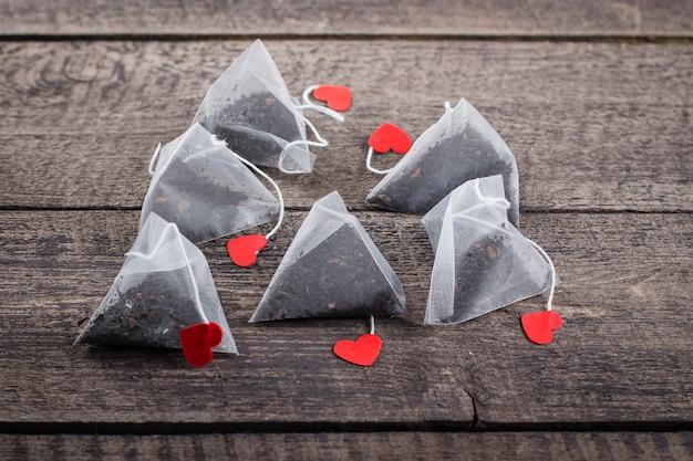 Sachets de thé pyramid avec forme de l'étiquette des coeurs sur fond de table en bois.