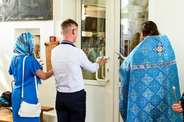 Le sacrement du baptême. baptême orthodoxe. prêtre avec des attributs rituels.