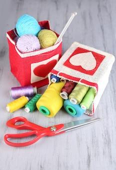 Sacs avec des bobines de fil coloré et des boules de laine sur bois