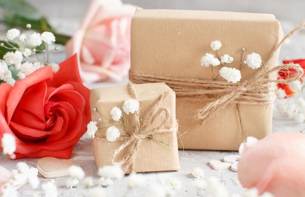 Sacs-cadeaux et fleurs - roses rouges et petites fleurs blanches sur fond gris