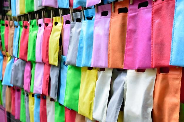 Sacs en cellophane suspendus avec une corde sur le mur. rangée de sacs en plastique colorés suspendus.