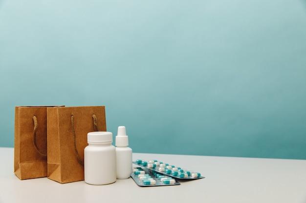 Sacs avec contenants et pilules médicaux blancs, thème des achats en ligne.