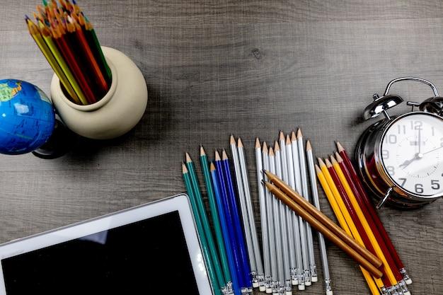 Sacs, crayons, livres utilisés dans des classes placées sur un plancher de bois.