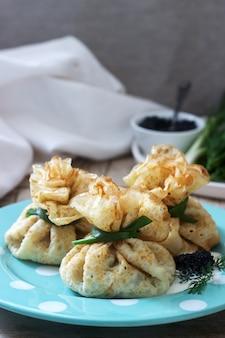 Sacs de crêpes farcies au hareng, servies avec du caviar, de la crème sure et de l'aneth sur un fond en bois. style rustique.