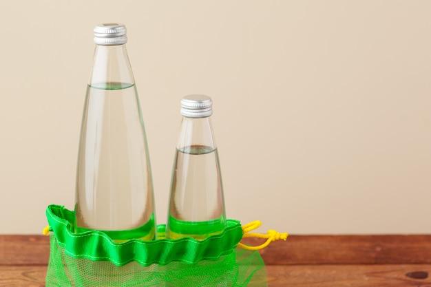 Sacs en filet avec bouteille d'eau en verre réutilisable.