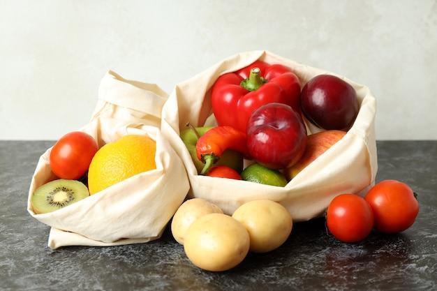 Sacs avec légumes et fruits sur table smokey noir