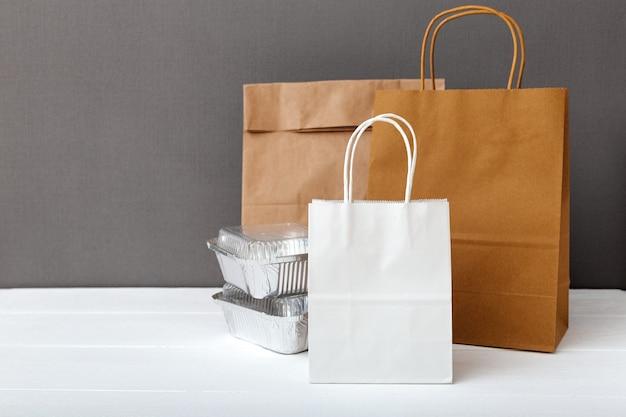 Sacs en papier artisanal blanc et contenants de nourriture sur fond gris tableau blanc. service de livraison de nourriture. aliments à emporter dans des contenants en aluminium, emballage de papier carton vide