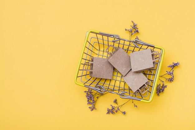 Sacs en papier artisanaux écologiques dans un panier en métal et fleurs séchées à côté sur fond jaune. black friday, vente de cadeaux. vue de dessus