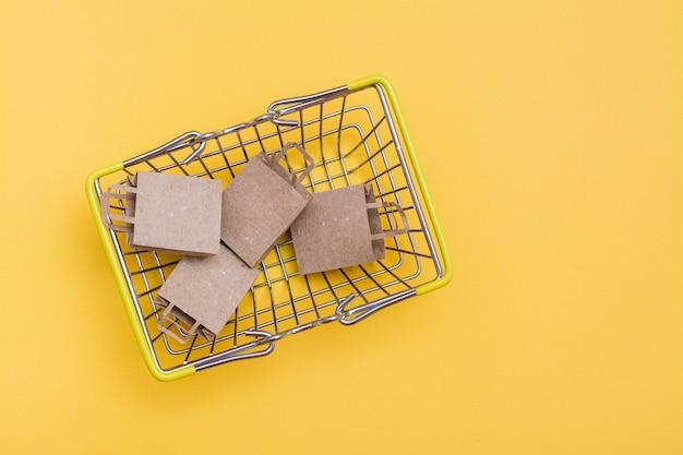 Sacs en papier artisanaux écologiques dans un panier en métal sur fond jaune. black friday, vente de cadeaux. vue de dessus