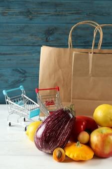 Sacs en papier, chariots, légumes et fruits sur table en bois