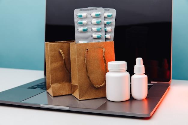 Sacs en papier de concept de pharmacie en ligne avec des médicaments sur ordonnance et des pilules et des contenants blancs sur un ordinateur portable