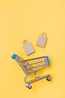 Des sacs en papier kraft écologiques tombent dans un caddie en métal sur fond jaune. black friday, vente de cadeaux. vue de dessus et verticale
