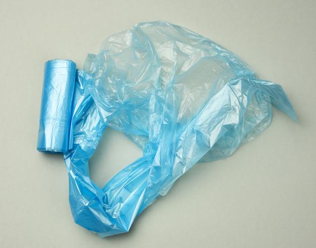 Sacs en plastique bleu tordu pour bac sur fond gris, vue du dessus