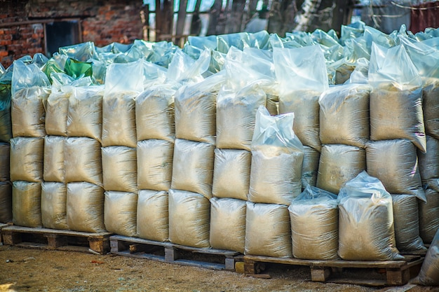 Les sacs en plastique avec du sable et de la terre sont rangés les uns sur les autres
