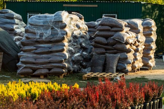 Sacs en plastique avec écorce de chêne et copeaux de bois pour la décoration des allées et des parterres de fleurs pliés sur des palettes pour le transport en jardinerie