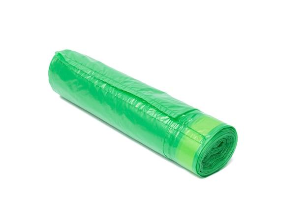Sacs poubelle en plastique vert avec des cordes isolés sur une surface blanche, gros plan