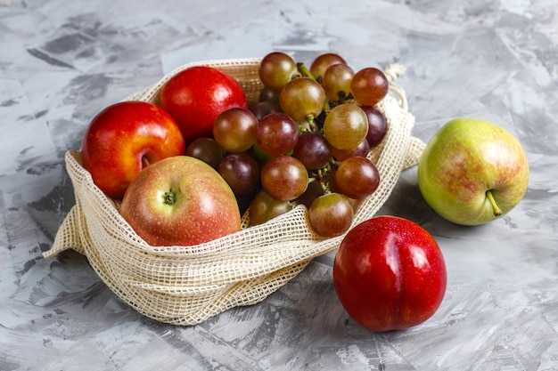 Sacs à provisions écologiques simples en coton beige pour acheter des fruits et légumes avec des fruits d'été.