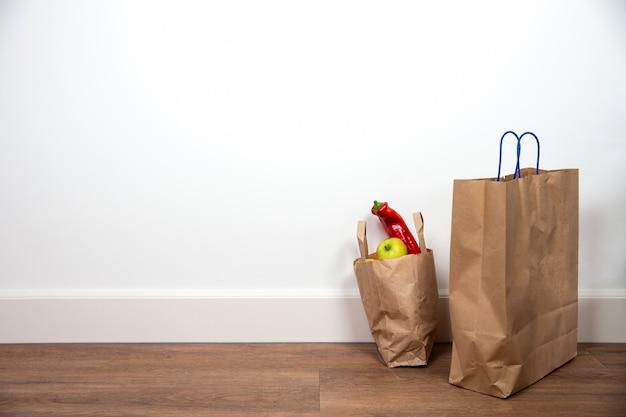 Sacs à provisions marron avec des légumes et des fruits contre le mur blanc, espace pour le texte