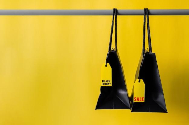 Sacs à provisions noirs avec des étiquettes de prix jaunes accrochés sur un support en tissu avec un fond jaune pour le concept de vente de shopping black friday.