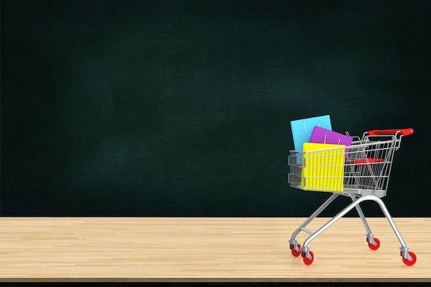 Sacs à provisions en papier coloré dans le chariot sur la table en bois avec toile de fond de tableau noir