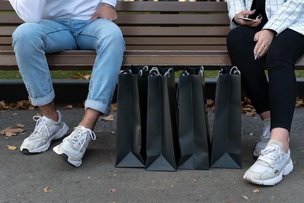Sacs à provisions en papier à côté des acheteurs reposant sur un banc. pieds de jeune homme et femme après le shopping.