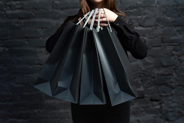 Sacs à provisions en papier noir dans des mains féminines sur fond noir. concept de vendredi noir.