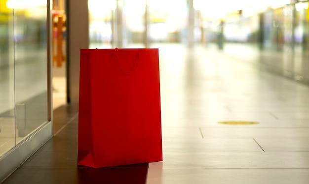 Sacs à provisions en papier rouge debout sur le fond du centre commercial