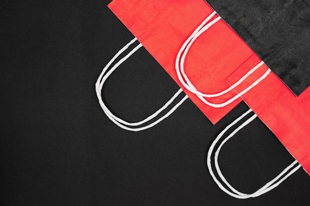 Sacs à provisions en papier rouge et noir sur fond noir. espace de copie. concept minimal de vente de vendredi noir
