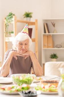 Sad senior female in birthday cap à la recherche de plats faits maison alors qu'il était assis par table servie