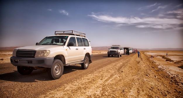 Safari et voyage vers des aventures africaines extrêmes dans le désert du sahara. panne de jeep sous un soleil brûlant au milieu d'un marais salé, d'une route déserte et de véhicules tout-terrain