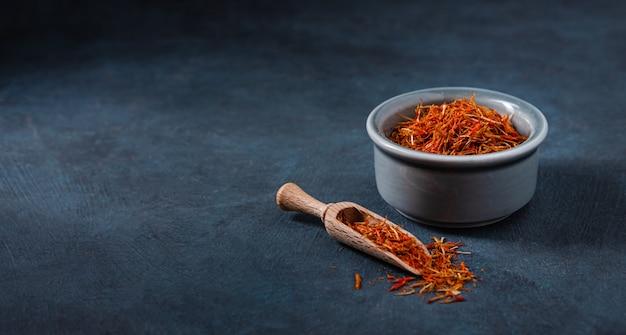 Safran d'épices orientales dans un bol en céramique bleu sur une table sombre. copier l'espace