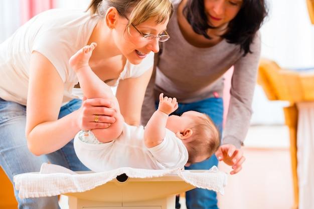 Sage-femme mesurant le poids ou le nouveau-né