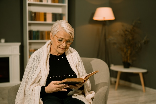 Sage senior woman in eyeglasses reading old book