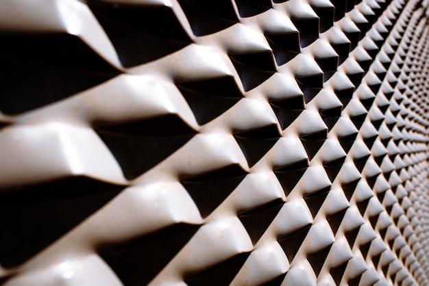 Des saillies métalliques diagonales industrielles illuminées par une lumière intense et des ombres intenses.