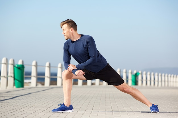 Sain jeune homme étirement exercice en plein air