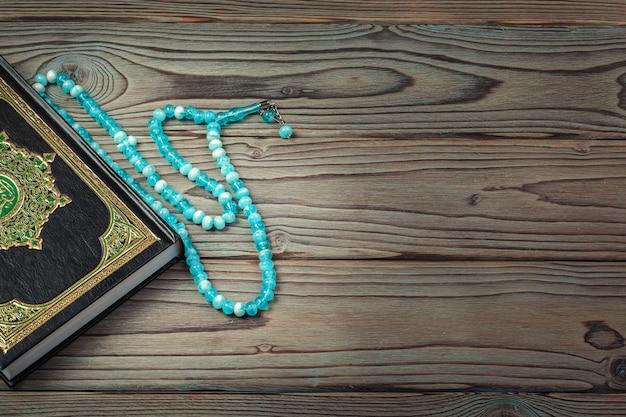 Saint coran avec des perles sur une surface en bois