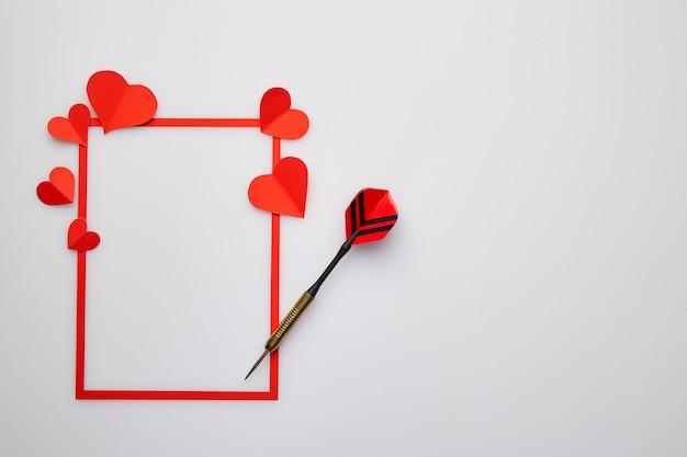 Saint valentin aux fléchettes rouges et au coeur de papier