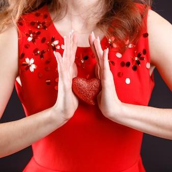 La saint-valentin. belle jeune femme avec coeur dans ses mains. jeune femme avec coeur rouge sur fond noir. portrait de jolie femme souriante studio tourné avec coeurs. fermer