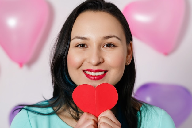 La saint-valentin. belle jeune femme avec coeur dans ses mains. jeune femme avec coeur rouge sur mur blanc avec des ballons gonflables.