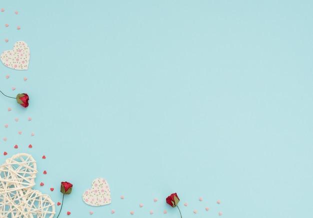 Saint valentin bleu avec des coeurs en rotin et feutre, des roses rouges et des petits coeurs rouges et roses