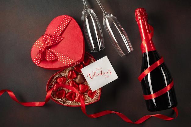 Saint valentin avec une boîte de chocolats en forme de coeur avec une bouteille de champagne avec des verres et une note