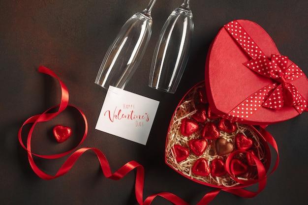 Saint valentin avec une boîte ouverte de chocolats en forme de coeur avec une bouteille de champagne avec des lunettes et une note