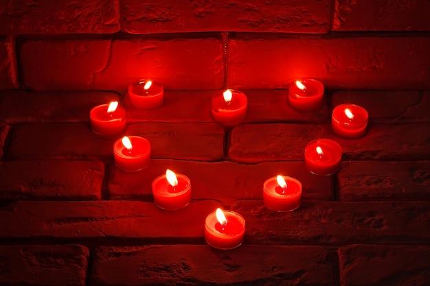 Saint-valentin bougies allumées en forme de coeur debout sur une vieille surface en pierre.