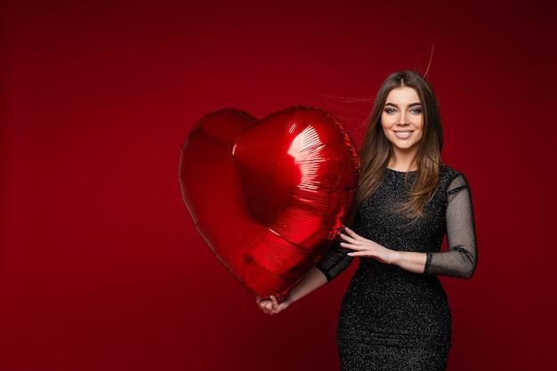 Saint-valentin célébrant la jeune fille avec ballon coeur sur rouge