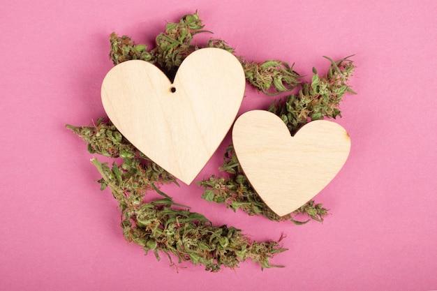 Saint valentin avec des coeurs en bois de marijuana et du cannabis récréatif