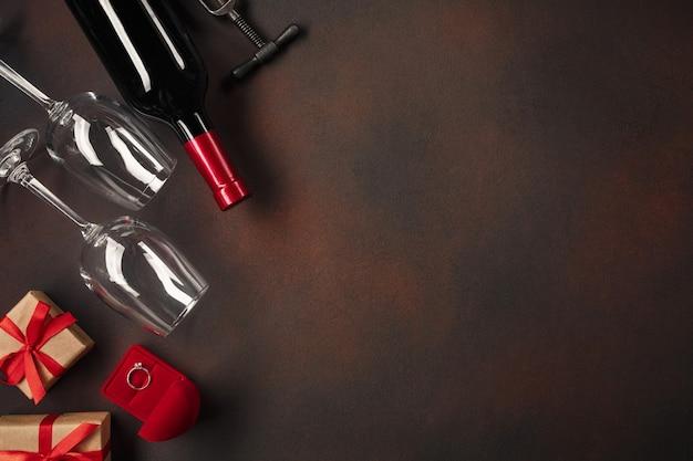 Saint valentin avec des cœurs, du vin, des verres, des cadeaux, une boîte en forme de cœur et un tire-bouchon