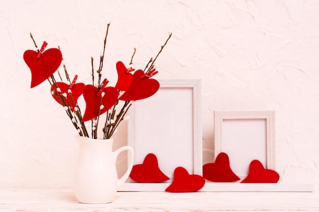 La saint-valentin. coeurs en feutre rouge sur les branches de saule dans une cruche blanche sur la table et vide cadre photo.