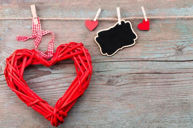Saint valentin avec des coeurs rouges et un tableau noir sur des planches en bois.