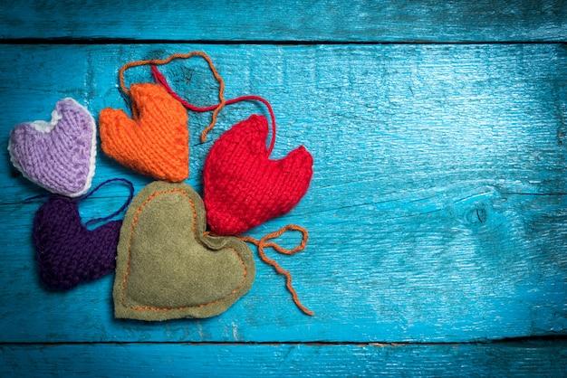 La saint-valentin. coeurs tricotés colorés. coeur rouge sur les planches bleues. la saint-valentin. pendentif coeur. coeur rouge. cartes de saint valentin.