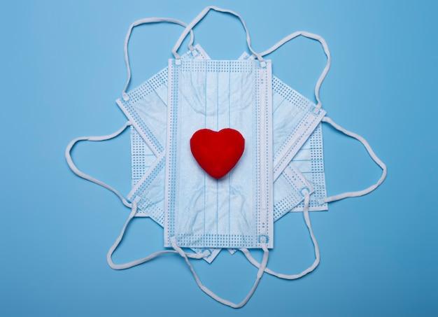La saint-valentin. coronavirus valentine. masques médicaux et coeur rouge.